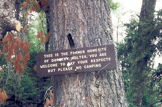 """Sign pinned to a tree on the Isle of Pines that states, """"This is the former homesite of Dorothy Molter. You are welcome to pay your respects but please no camping."""""""